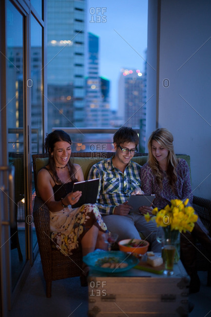Three people sitting together on a couch on a balcony of a city apartment, with a tablet