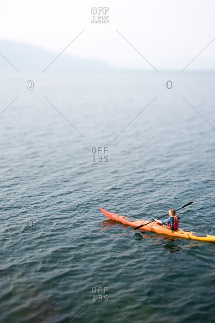Woman kayaking on an Idaho Lake in late summer