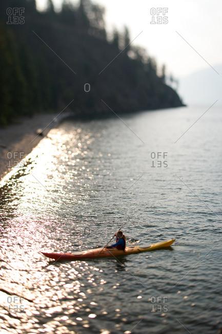 Woman kayaking to shore on an Idaho Lake in late summer