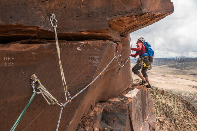A man rock climbing a desert sandstone tower called Psycho Babble Tower in the Big Gypsum Valley near, Naturita, Colorado