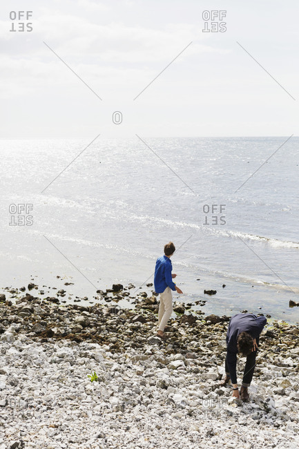 Two young men throwing rocks into the ocean