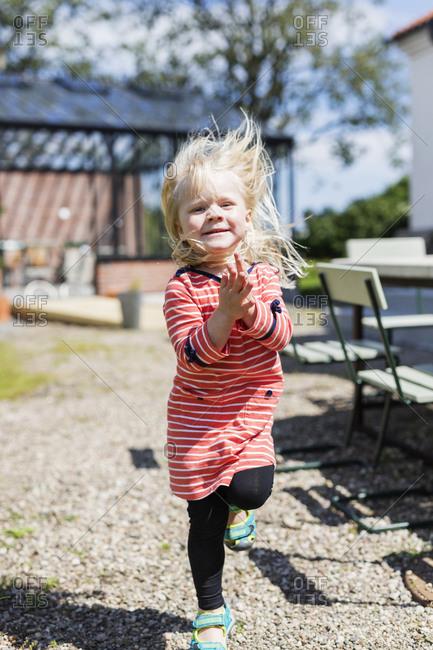 Little blonde girl running and skipping