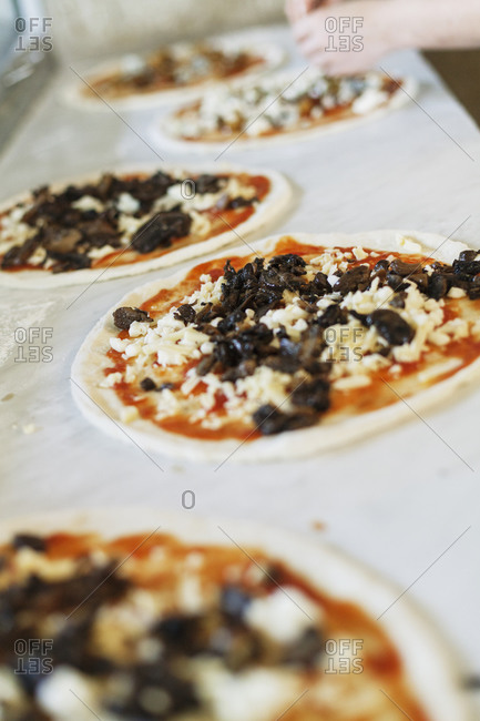 Sauce and toppings being put onto pizza crusts
