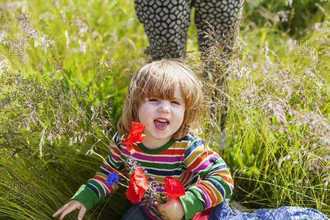 Little girl holding a bouquet of wild flowers