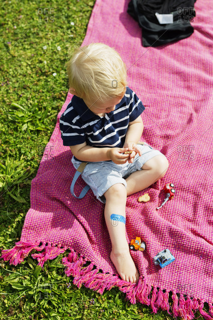 Boy sitting on blanket in grass playing with toy cars
