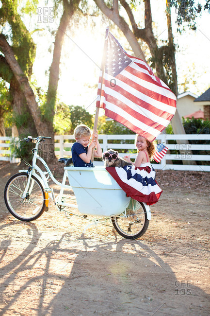 Boy and sister in basket of patriotic bike