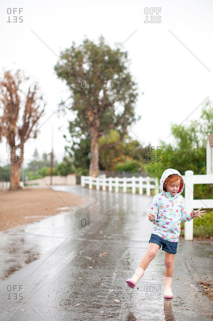 Girl in raincoat playing in the rain