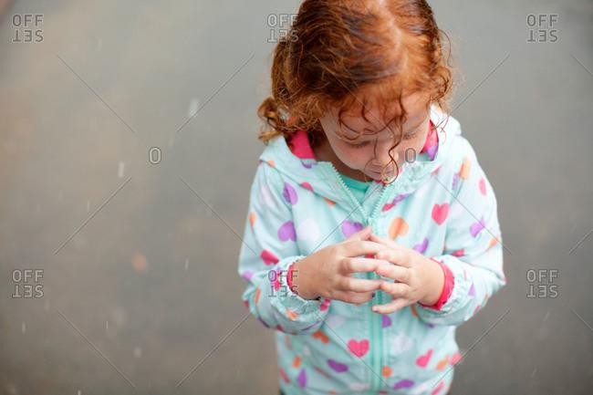 Girl in raincoat standing in rain drops