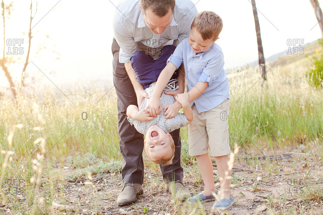 Boy getting tickled by man and boy in field