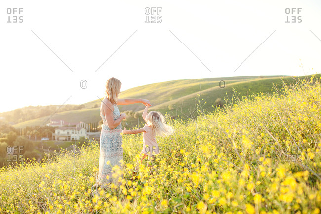 Girl dancing with mom in pastoral field