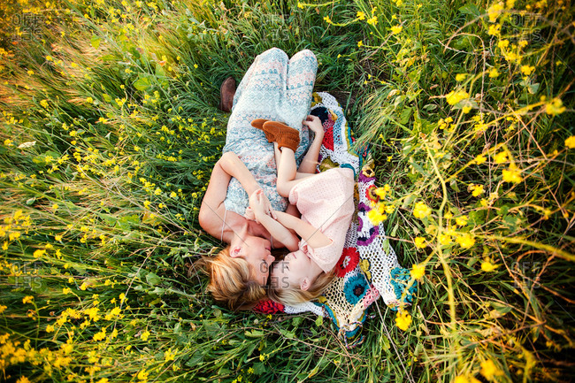 Mom and girl on blanket in wildflower field