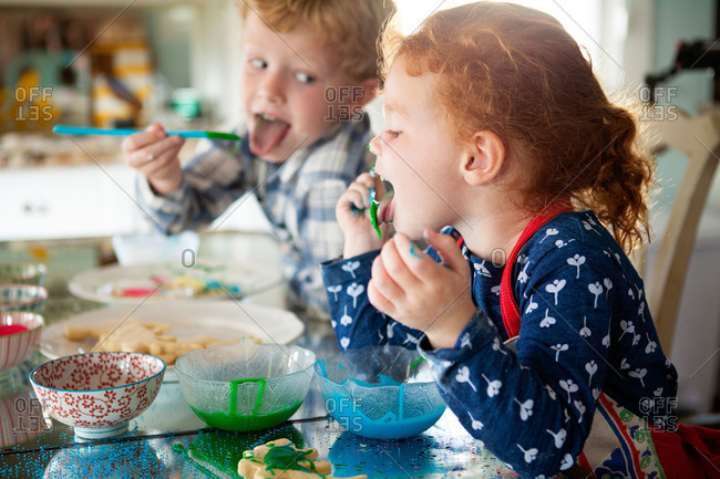 Kids eating icing while decorating cookies