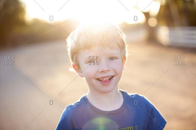 Smiling blonde boy in sun dappled rural setting