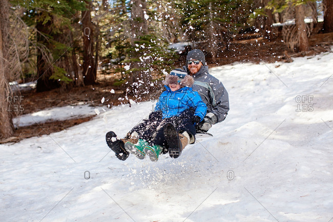 Dad and boy midair while sledding in woods