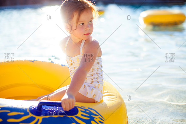 Girl on ring floatie gazing off