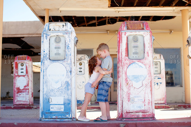 Girl hugging boy at an abandoned gas station