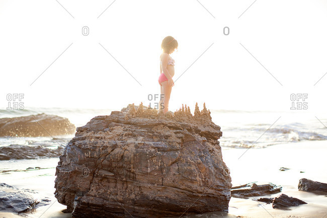 Girl on builder with mud drippings on beach