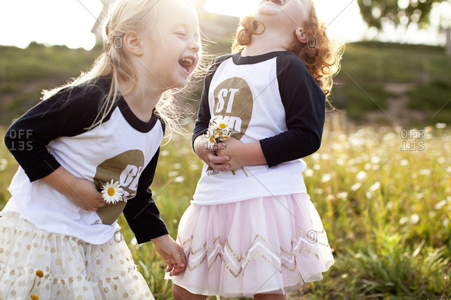 Girls in matching outfits giggling in rural setting