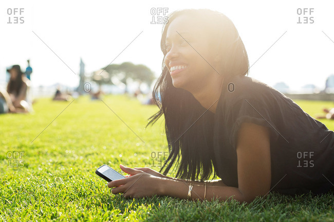 Woman lying on grass with her phone in sunlight