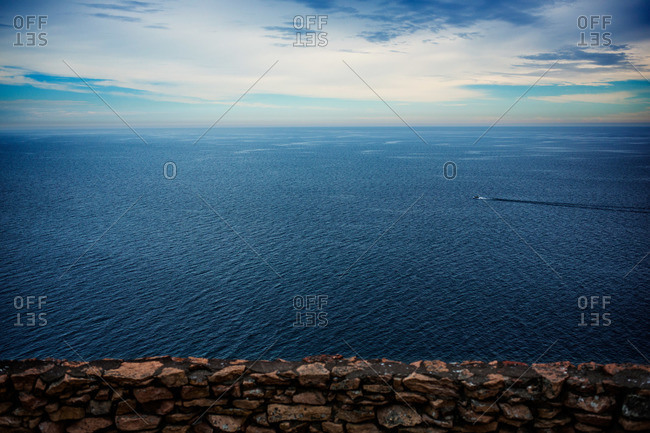Stone wall in front of vast blue ocean