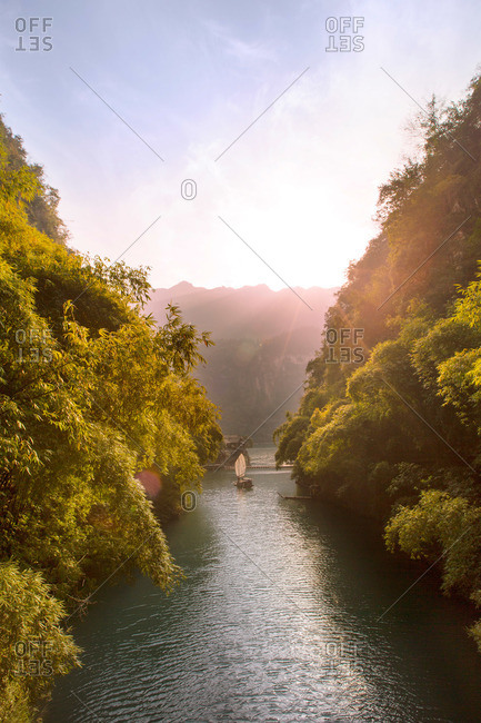 Boat in tree lined rugged waterway