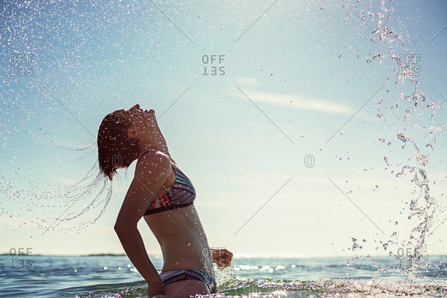 Woman in bikini splashing ocean water with hair