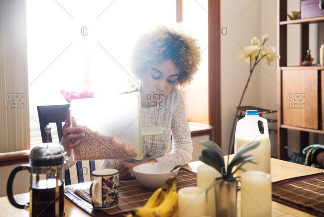 Sun dappled woman pouring cereal for breakfast