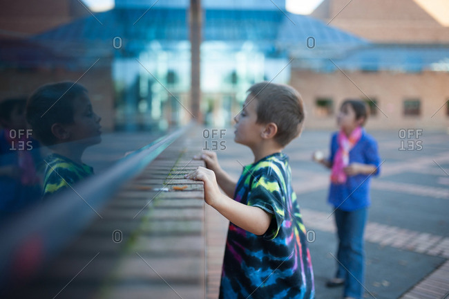 Young boy peeking into window of a building