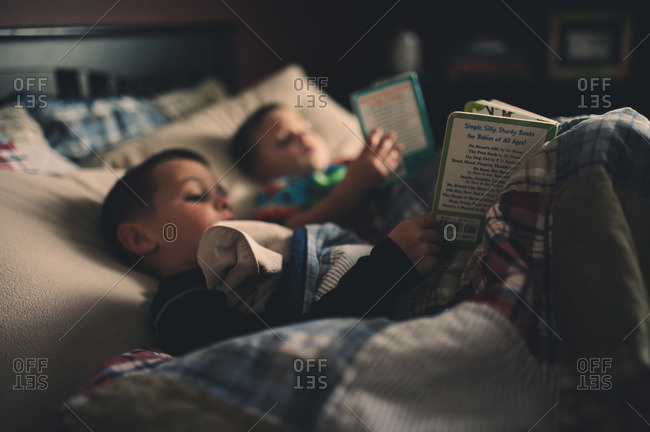 Two boys in a bed together reading