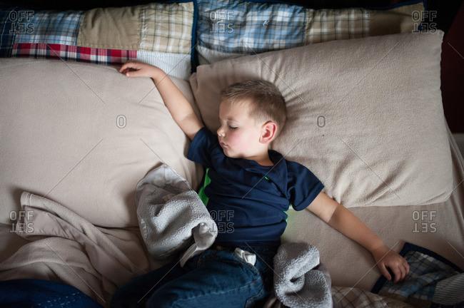 Boy sprawled out asleep on a bed
