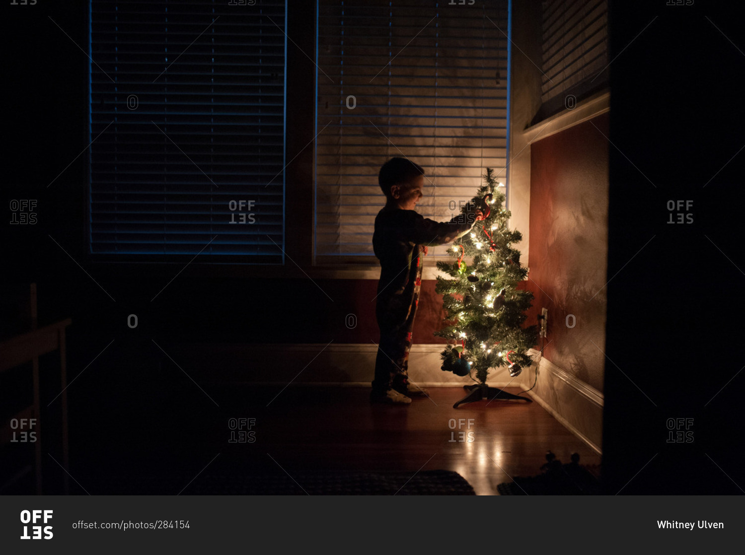 Boy by glowing little Christmas tree stock photo - OFFSET