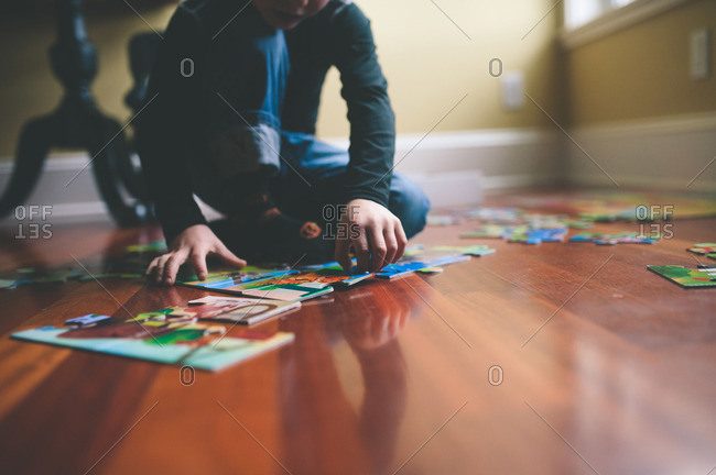 Boy sitting on the floor putting together puzzle