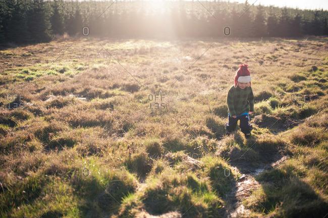 Boy in winter hat walking in rural field