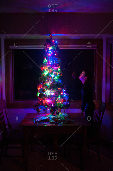 Boy looking at glowing Christmas tree on table