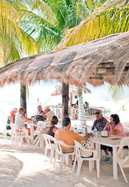 Isla Mujeres, Mexico - December 12, 2010: Tourists at beach restaurant on Isla Mujeres, Mexico