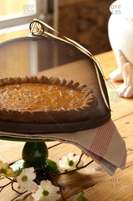 Sweet potato custard pie on a cake stand on a rustic table