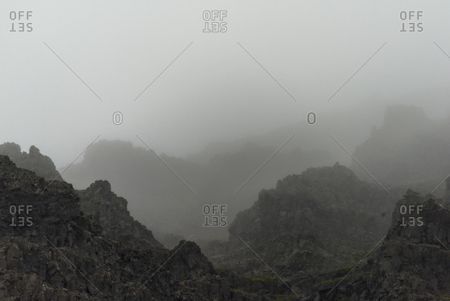 Jagged rocky peaks covered in mist in Iceland