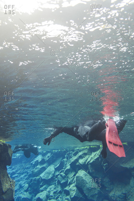 Diver swimming in tectonic rift in Iceland