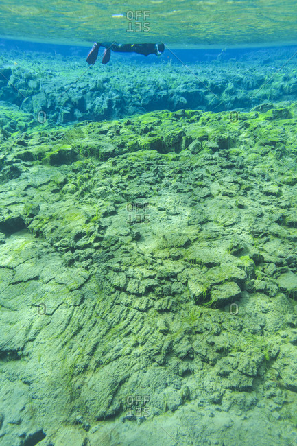 Diver swimming over tectonic rift in Iceland