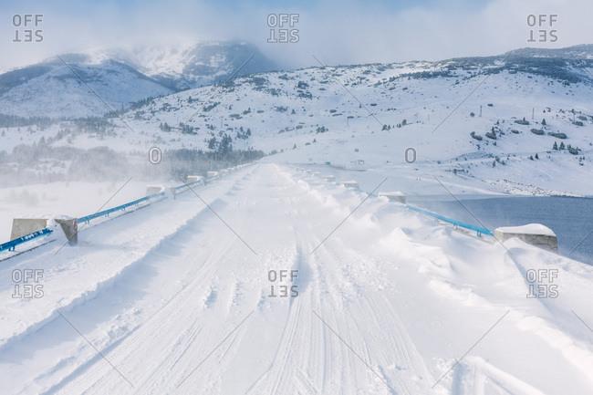 Snowy bridge during cold windy winter, Belmeken Dam, Rila Mountains, Bulgaria