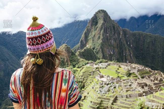 Female traveler looking at Machu Picchu citadel and Huayna mountain, Peru