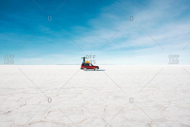 Man standing on his 4x4 in the Uyuni Salt Flats, Potosi, Bolivia