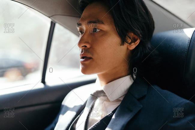 Businessman on back seat of car, New York City