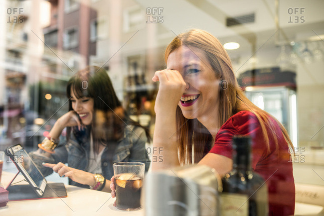 Two happy young women in a bar with drinks and digital tablet
