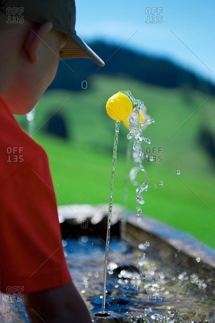 Boy playing with a small ball at fountain