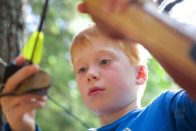 Portrait of a boy with a bow in an adventure park