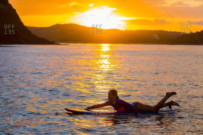 Woman lying on surfboard in the water, Bali