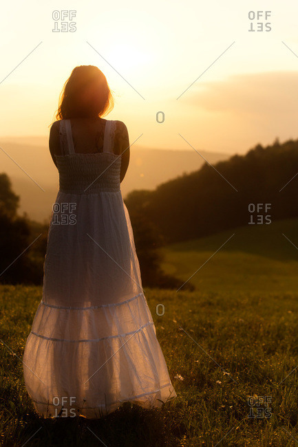 Back view of woman on Alpine meadow watching sunrise