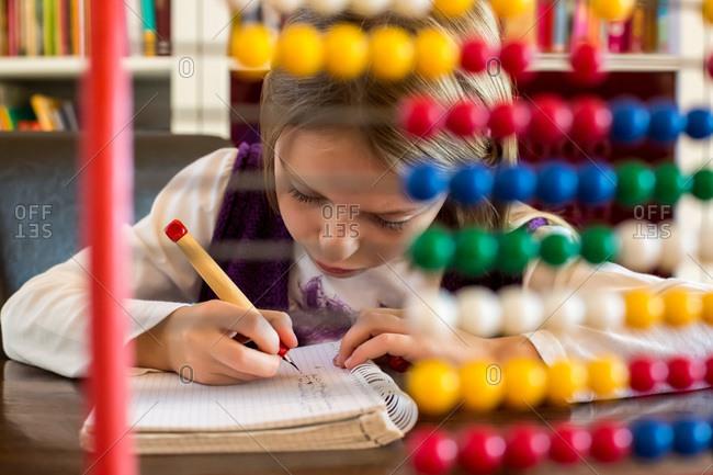 Girl sitting behind abacus doing homework