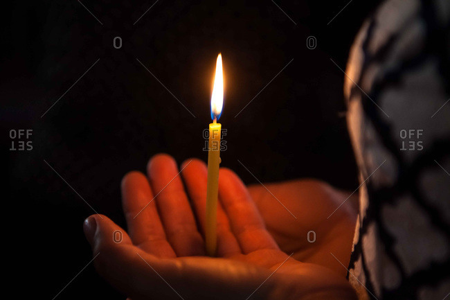 Candle burning in palm of hand